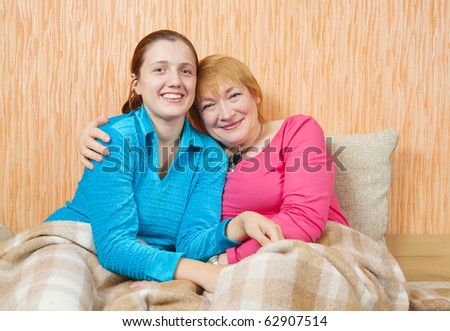 Happy woman and her adult daughter on sofa at home - stock photo