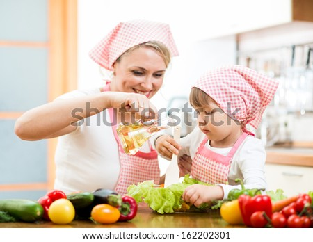 Happy woman and her daughter child preparing healthy food together - stock photo