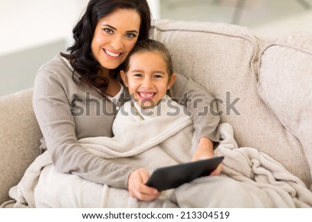 happy woman and her little daughter snuggle on couch wrapped with blanket - stock photo