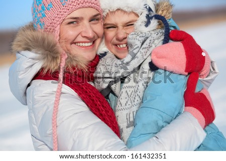 Happy woman and her son in winterwear looking at camera - stock photo