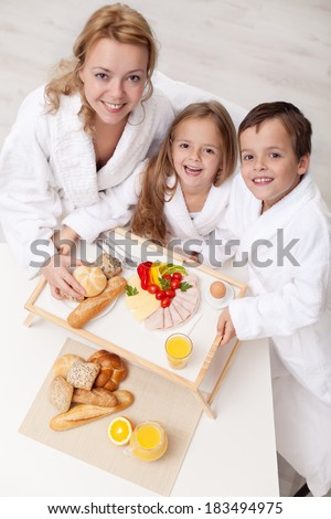 Happy woman and kids having a light and healthy snack together - stock photo