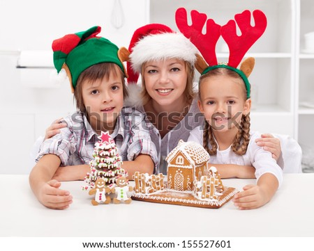 Happy woman and kids in christmas hats making gingerbread cookie