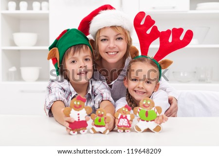 Happy woman and kids in christmas hats making gingerbread cookie family