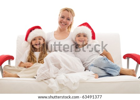 Happy woman and kids sitting on a sofa wearing christmas hats - isolated