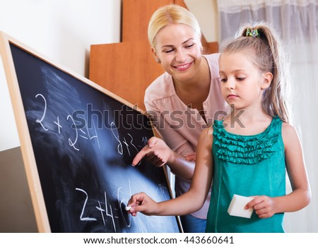 Happy woman and little daughter doing sum at blackboard indoors - stock photo