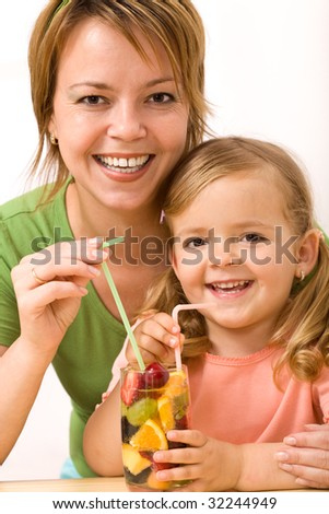Happy woman and little girl drinking a fruity refreshment  with straw - stock photo