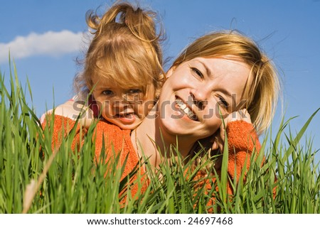 Happy woman and little girl laying in the fresh spring grass - closeup - stock photo