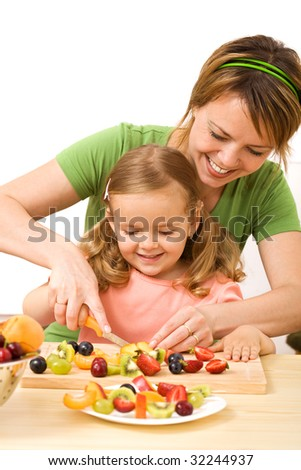 Happy woman and little girl slicing fruits for a healthy salad