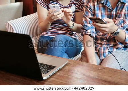 Happy woman and man hand point finger on phone and laptop on table,good relationship ,the internet of things.Two young business people touching on mobile phone while working and discussion at home. - stock photo