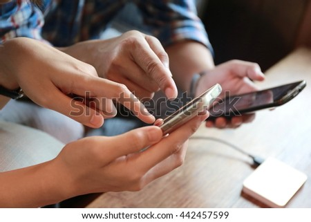 Happy woman and man hand point finger on phone on table,relationship ,the internet of things.Couple people touching on mobile phone while working and discussion, relaxing lifestyle, together