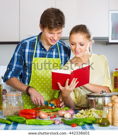 Happy woman and man preparing veggies meal in domestic kitchen
