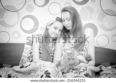 Happy woman and schoolgirl daughter sitting with cat at home - stock photo