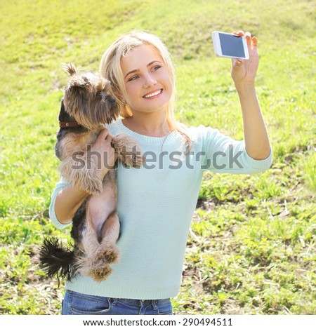 Happy woman and yorkshire terrier dog having fun takes selfie portrait on the smartphone - stock photo