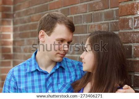 Happy woman and young man stand near brick wall and look at each other - stock photo
