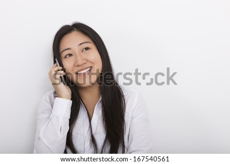 Happy woman answering cell phone against white background