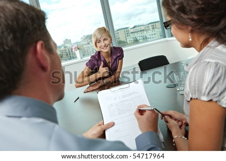 Happy woman applicant got the job by a successful job interview. Over the shoulder view. - stock photo