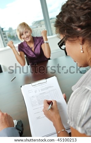 Happy woman applicant got the job by a successful job interview. Over the shoulder view. Focus placed on sheet in front, reults are excellent - stock photo