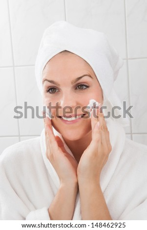 Happy Woman Applying Cream On The Face