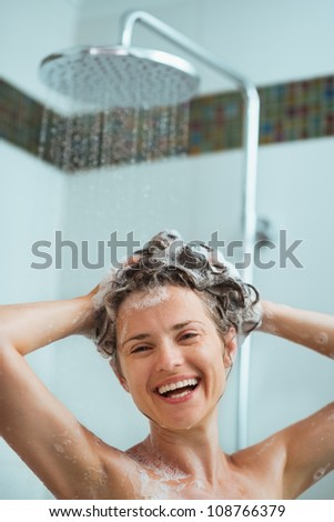 Happy woman applying shampoo in shower