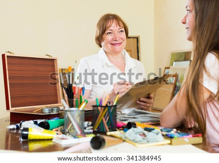 Happy woman artist painting a new picture - stock photo