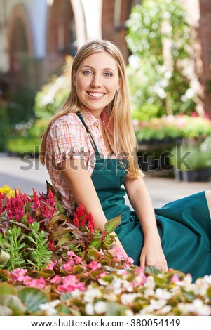 Happy woman as small business owner of a flower shop - stock photo