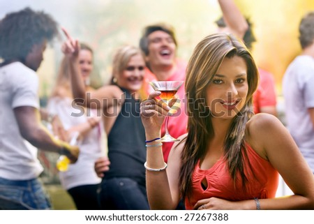 Happy woman at a party smiling and holding a cocktail drink - stock photo