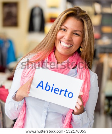 Happy woman at a retail store with an open sign smiling - stock photo