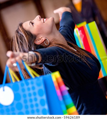 Happy woman at a shopping center holding bags with arms open