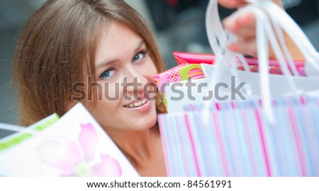 Happy woman at a shopping center holding bags with arms open. Seasonal preparty shopping boom - stock photo