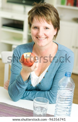 Happy woman at home holding apple and smiling at camera - stock photo