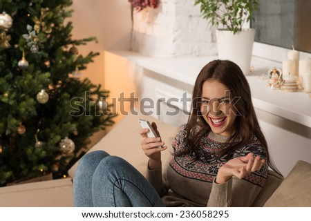 Happy woman at home reading a text message while sitting on sofa