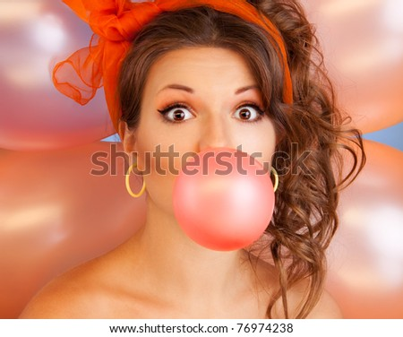 Happy woman at party blowing bubblegum bubble with air baloons on background