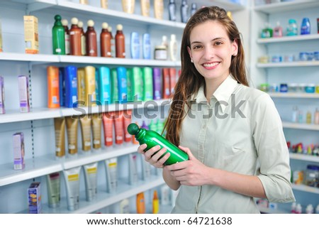happy woman at pharmacy buying shampoo - stock photo