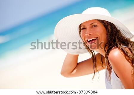 Happy woman at the beach wearing a hat on a summer day - stock photo