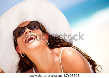 Happy woman at the beach wearing hat and sunglasses - stock photo