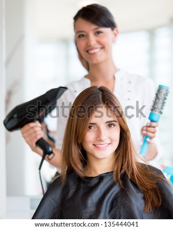 Happy woman at the beauty salon getting a hair cut - stock photo