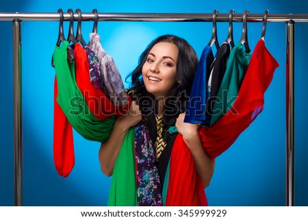 Happy Woman At The Clothing Rack With Dresses On Blue Background - stock photo