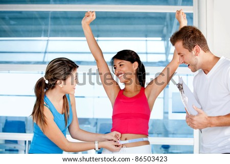 Happy woman at the gym with her trainers measuring her body ? weight loss - stock photo