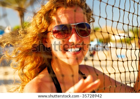 happy woman behind the volleyball net - stock photo