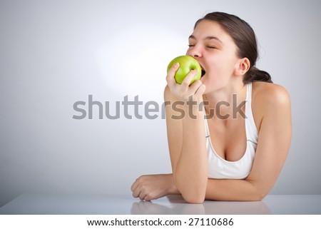 Happy woman biting a green apple - stock photo