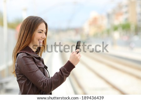 Happy woman browsing social media in a train station with the railways in the background     - stock photo