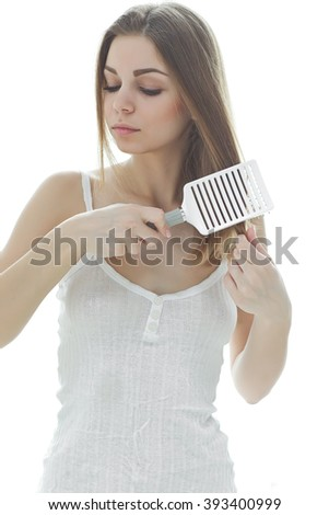 Happy woman brushing her beautiful healthy wavy hair