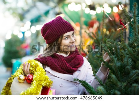 Happy woman buying Christmas tree in the market
