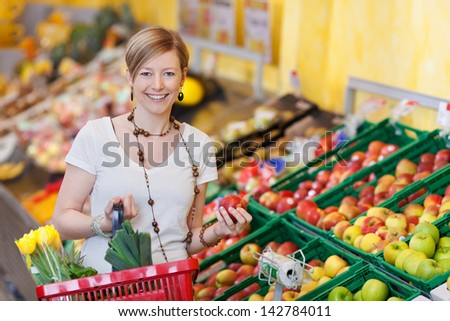 Happy woman buying fresh produce in a supermarket standing with a basket of groceries in one hand and a ripe red apple in the other - stock photo