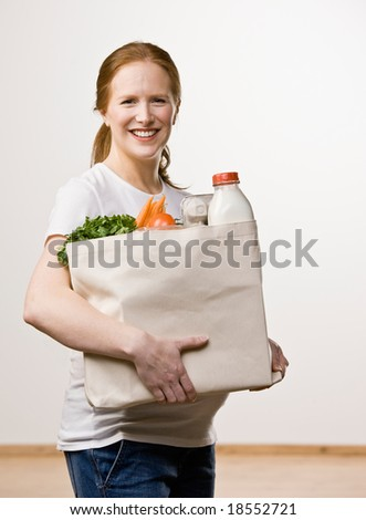 Happy woman carrying grocer bag of wholesome fruits, vegetables and milk