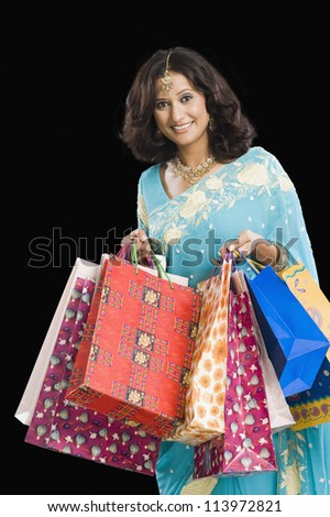Happy woman carrying shopping bags - stock photo