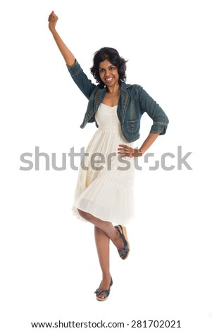 Happy woman celebrates by cheering and dancing in studio, isolated on white
