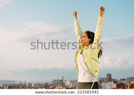Happy woman celebrating fitness and sport exercising success. Successful female athlete raising arms to the sky on city skyline background. - stock photo