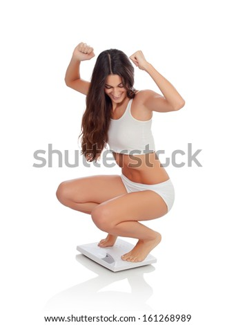 Happy woman celebrating her new weight on a scale isolated on a white background - stock photo