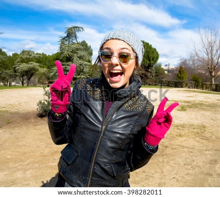 Happy woman cheering joyful during holiday travel.Portrait of beautiful cool girl gesturing in hat and sunglasses in the park,tourism and travel.Happy traveler. - stock photo